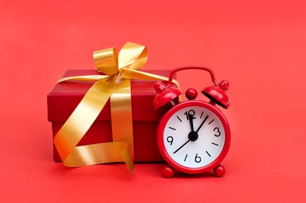 Despertador vermelho e caixa de presente vermelha em fundo vermelho