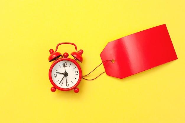 Despertador vermelho e etiqueta vermelha em branco para inscrição em fundo amarelo