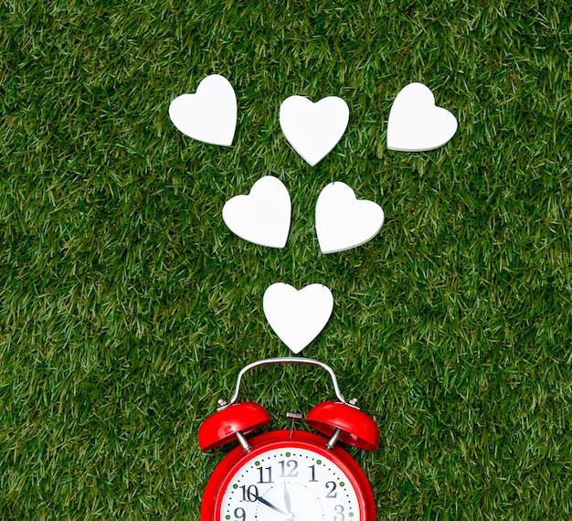Despertador vermelho e formas de coração na grama verde.