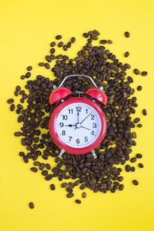 Despertador vermelho e grãos de café no fundo amarelo. localização vertical.
