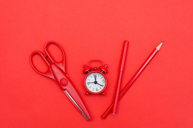 Despertador vermelho e material escolar em fundo vermelho