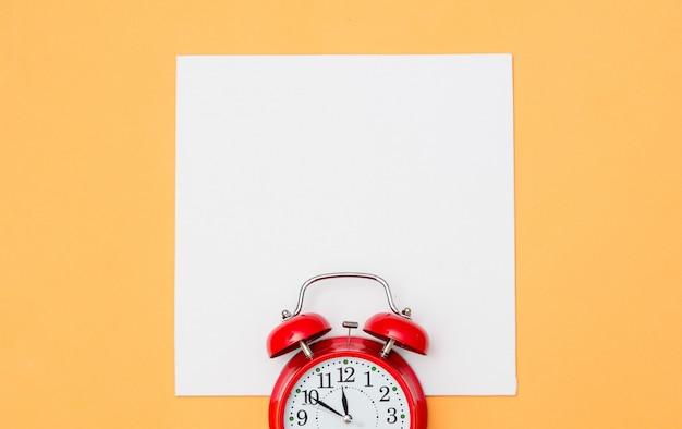 Despertador vermelho e papelão branco sobre amarelo