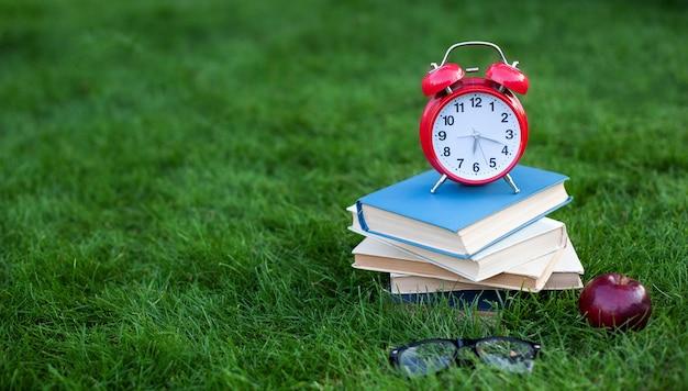 Despertador vermelho e pilha de livros antigos no parque na manhã de outono