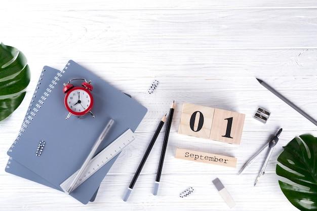 Despertador vermelho e suprimentos, calendário de madeira com data na mesa branca. de volta ao conceito de escola. colocação plana.