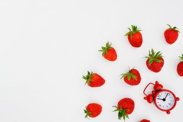 Despertador vermelho e voar dispersando morangos berry no fundo branco