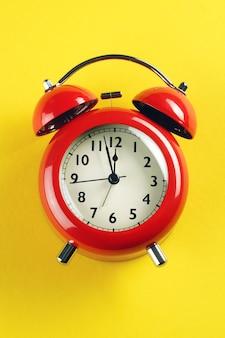 Despertador vermelho em estilo retro, sobre um fundo amarelo brilhante