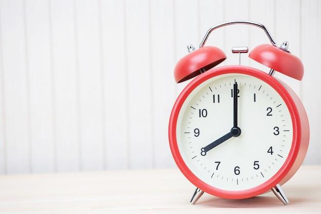 Despertador vermelho marcado para três, isolado sobre fundo branco