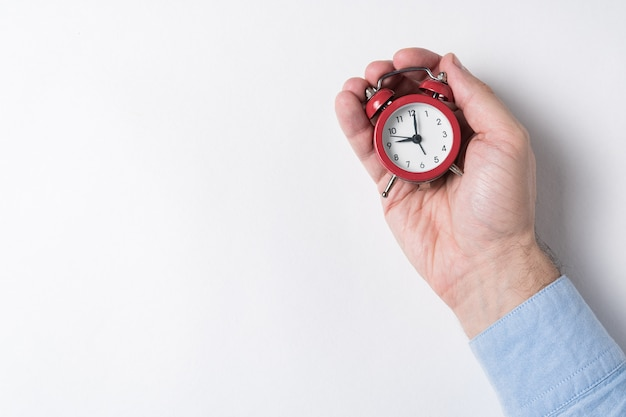 Despertador vermelho mecânico nas mãos masculinas no fundo branco. conceito de gerenciamento de tempo. vista do topo