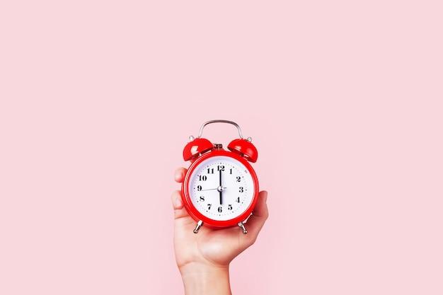 Despertador vermelho na mão, sobre fundo rosa, conceito de tempo para se levantar