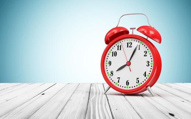 Despertador vermelho na mesa de madeira
