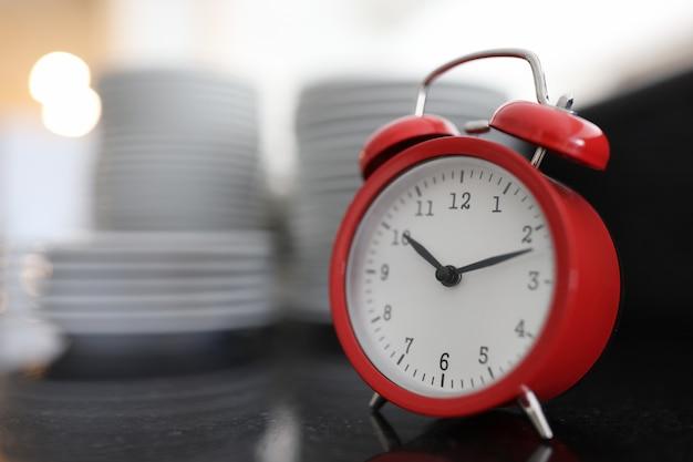 Despertador vermelho no fundo de uma grande pilha de pratos de café da manhã em hotéis e café conceito