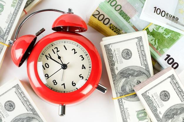 Despertador vermelho retrô e pilhas de notas de dólar e euro