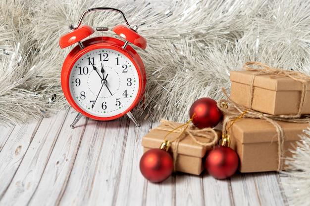 Despertador vermelho vintage e três caixas de presente em uma mesa de madeira decorada com uma guirlanda e bolas vermelhas de natal para o ano novo ou natal. copie o espaço