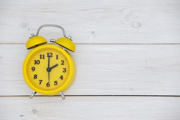 Despertador vintage amarelo na vista superior do fundo branco de madeira
