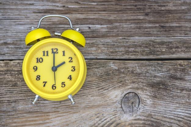 Despertador vintage amarelo na vista superior do plano de fundo de madeira