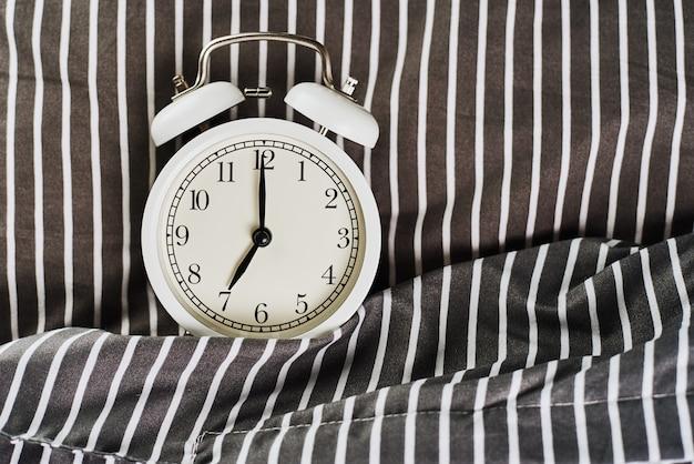 Despertador vintage branco no travesseiro na cama. wale up e conceito de manhã
