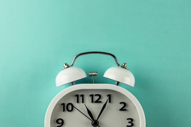 Despertador vintage branco sobre fundo azul