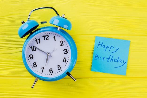 Despertador vintage e desejo de feliz aniversário. vista superior plana lay. fundo de madeira amarelo.