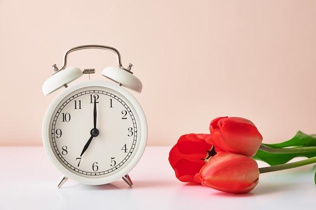 Despertador vintage e flores de tulipas em um vaso no fundo branco primavera, economizando tempo conceito de manhã
