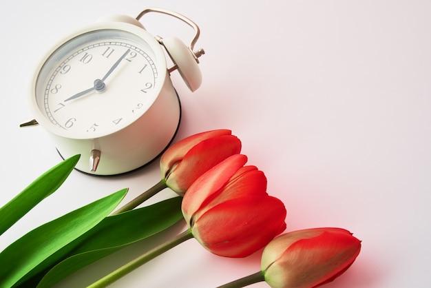 Despertador vintage e flores de tulipas em um vaso no fundo branco