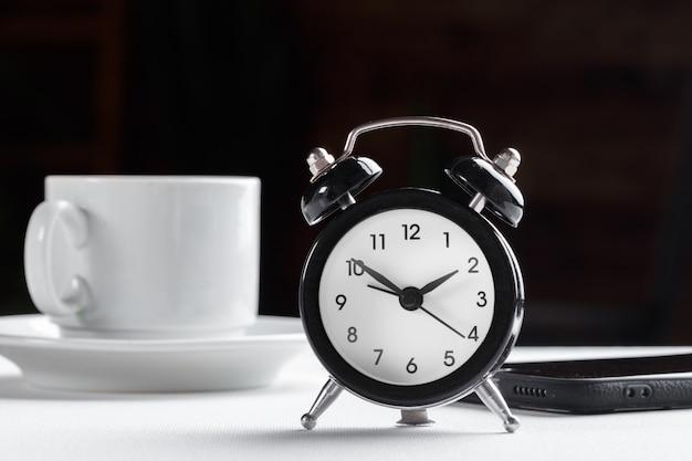 Despertador vintage e xícara de café na mesa branca