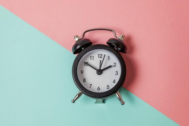 Despertador vintage isolado em fundo pastel azul e rosa