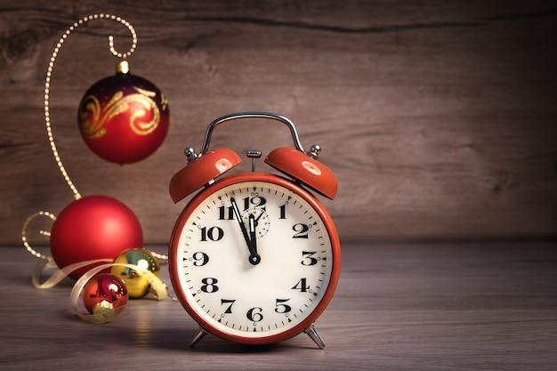 Despertador vintage mostrando cinco a doze e enfeites de natal em madeira.