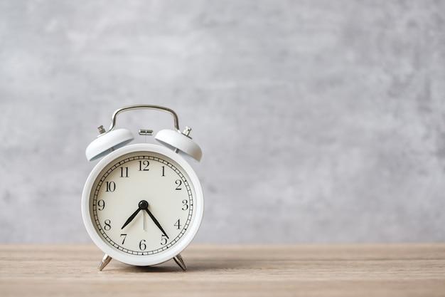 Despertador vintage no fundo da mesa de madeira e copie o espaço para o texto. conceito de atividade, rotina diária, manhã, contagem regressiva, treino e equilíbrio entre vida profissional