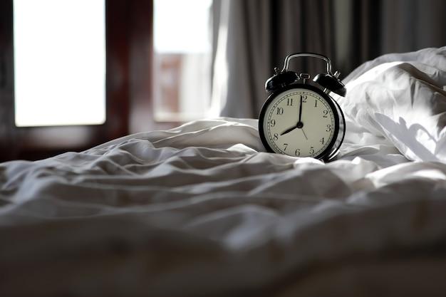 Despertador vintage no quarto pela manhã com luz do sol nas janelas