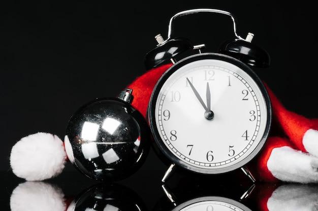 Despertador vintage preto com enfeites de natal e decoração em fundo preto escuro