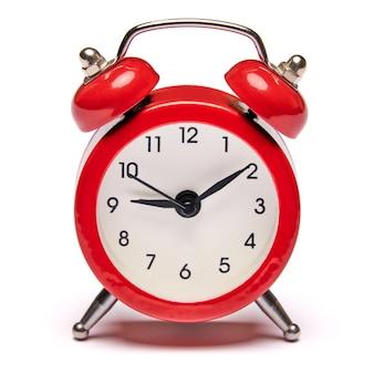 Despertador vintage vermelho isolado na parede branca com traçado de recorte