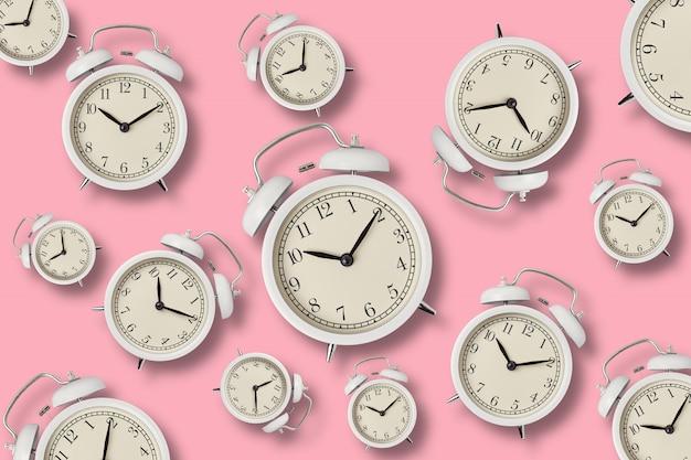 Despertadores brancos do vintage com sombras no fundo rosa, vista superior mínima styly