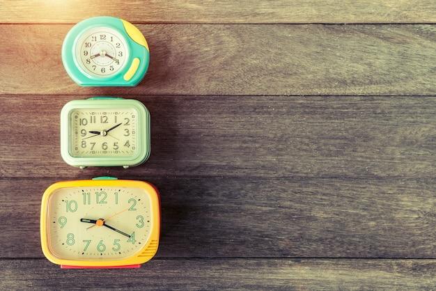 Despertadores retros na tabela de madeira. cor retrô ou vintage filtrada. conceito de tempo antigo.