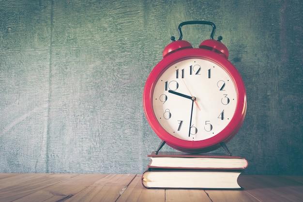 Despertadores vintage vermelhos com o quadro-negro atrás na mesa de madeira