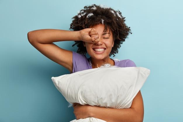 Despertar de bom humor. mulher negra alegre com cabelo encaracolado, esfrega os olhos, tem um sorriso largo no rosto, carrega um travesseiro macio, usa uma camiseta casual, tem um sono saudável, penas nos cachos, gosta do tempo matinal