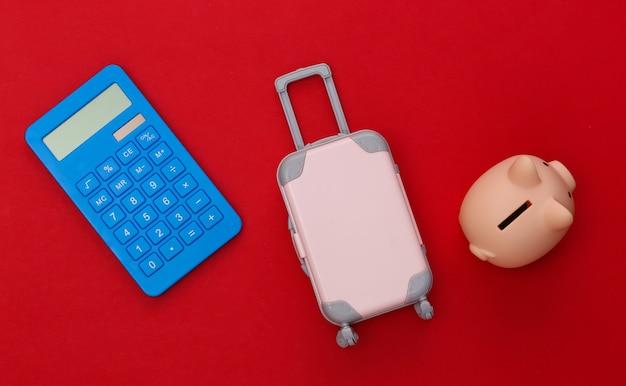 Despesas de viagem. mini mala de viagem de plástico com calculadora, cofrinho sobre fundo vermelho. vista do topo. postura plana