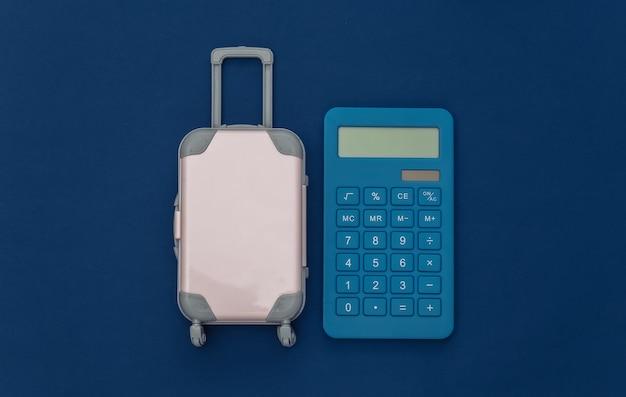 Despesas de viagem. mini mala de viagem de plástico com calculadora em fundo azul clássico. vista do topo. postura plana