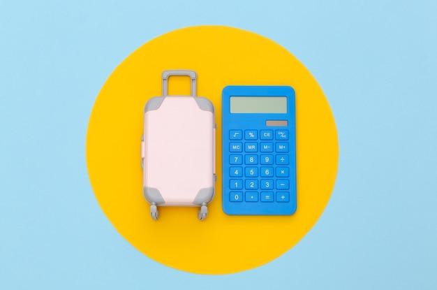 Despesas de viagem. mini mala de viagem de plástico com calculadora em fundo azul com círculo amarelo. vista do topo. postura plana
