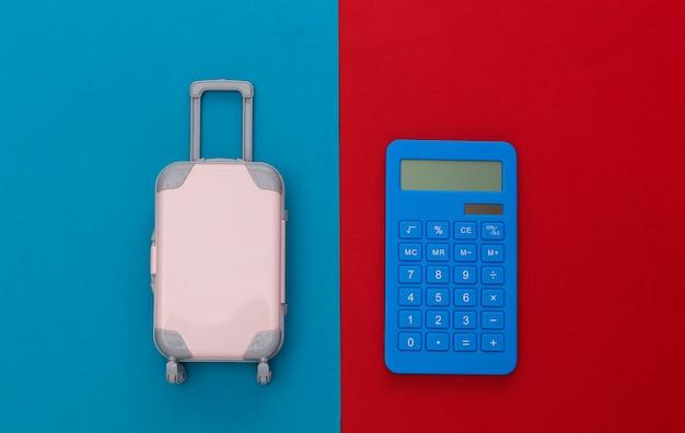 Despesas de viagem. mini mala de viagem de plástico com calculadora em fundo azul vermelho. vista do topo. postura plana