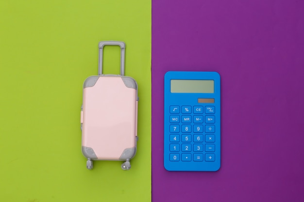 Despesas de viagem. mini mala de viagem de plástico com calculadora em fundo roxo verde. vista do topo. postura plana