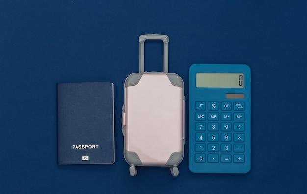 Despesas de viagem. mini mala de viagem de plástico com calculadora, passaporte com fundo azul clássico. vista do topo. postura plana