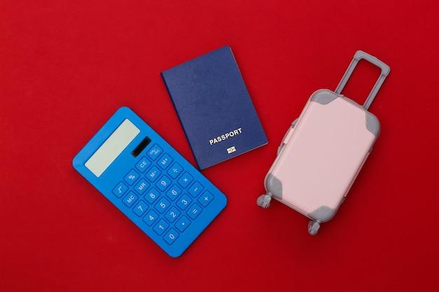 Despesas de viagem. mini mala de viagem de plástico com calculadora, passaporte com fundo vermelho. vista do topo. postura plana