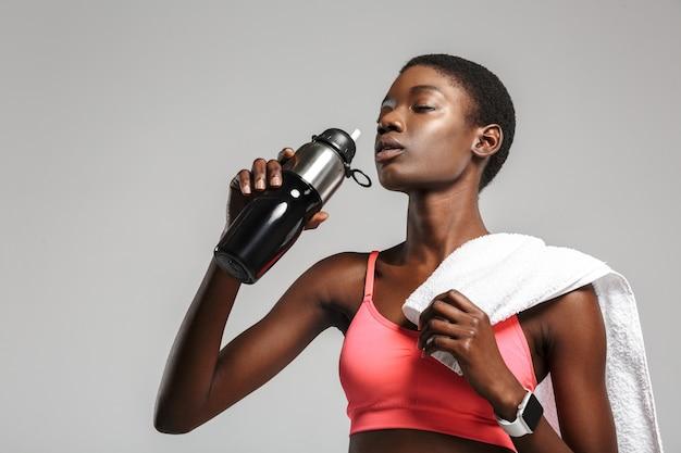 Desportista afro-americana com toalha de água potável enquanto malharia isolada sobre uma parede branca