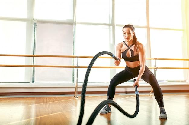 Desportista asiática malhando com cordas de batalha no ginásio