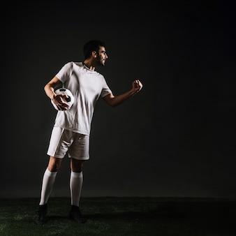 Desportista atraente com bola comemorando a vitória
