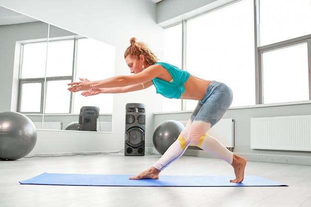 Desportista atraente fazendo exercícios no chão, no estúdio de paladares moderno. linda garota esportiva relaxando e esticando as pernas e os braços
