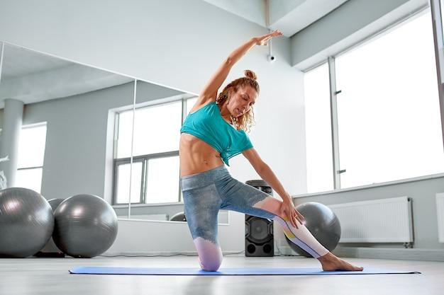 Desportista atraente fazendo exercícios no chão, no estúdio de pilates moderno. linda garota esportiva relaxando e esticando as pernas e os braços