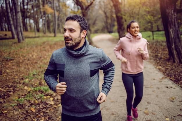 Desportista barbudo caucasiano positivo correndo na natureza com a namorada.