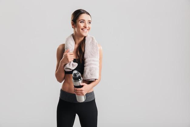 Desportista bonita saudável, vestindo agasalho com toalha, olhando de lado e segurando a garrafa com água fresca, isolada sobre a parede cinza