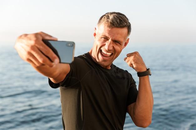 Desportista bonito alegre sem camisa a tirar uma selfie
